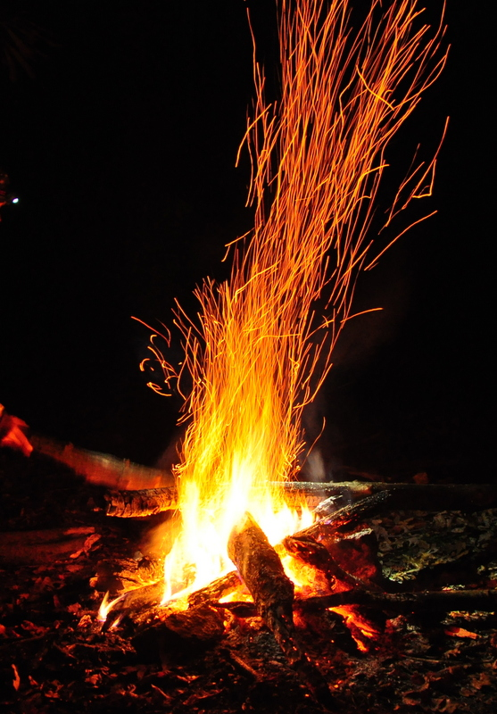 Campfire sparking embers at night on Appalachian Trail