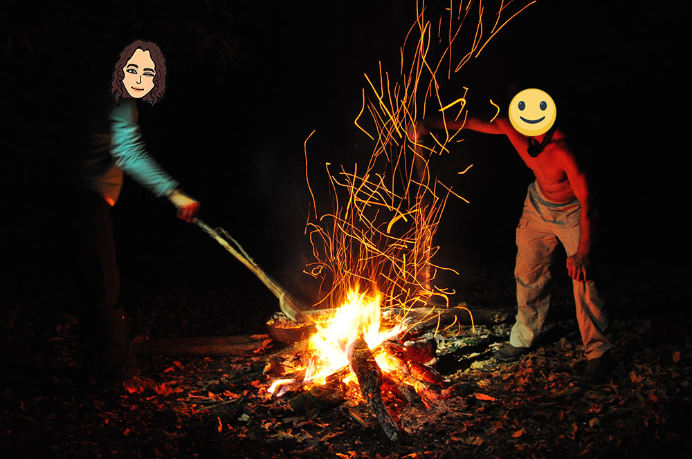 Stoking a sparking campfire at night in the forest
